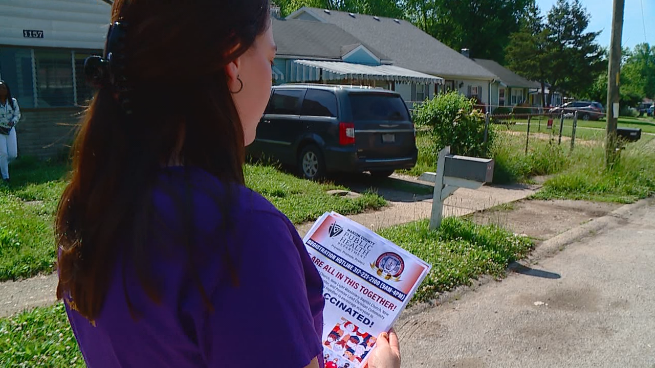 A volunteer walks through a neighborhood in Indianapolis delivering flyers advertising a COVID-19 vaccine clinic