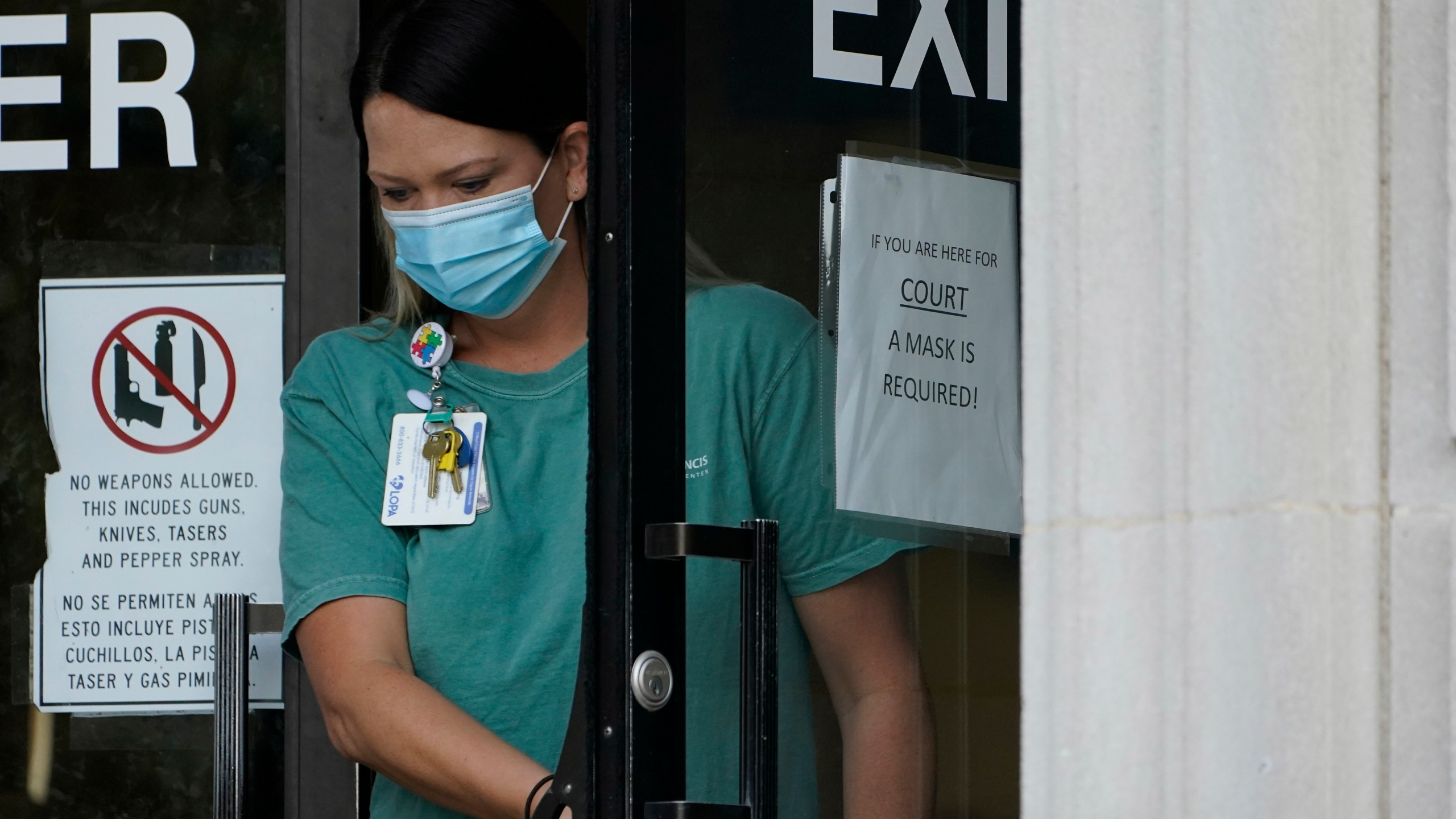 An individual wearing a face mask exits the Ouachita Parish Courthouse in Monroe, La., Thursday, Aug. 5, 2021.