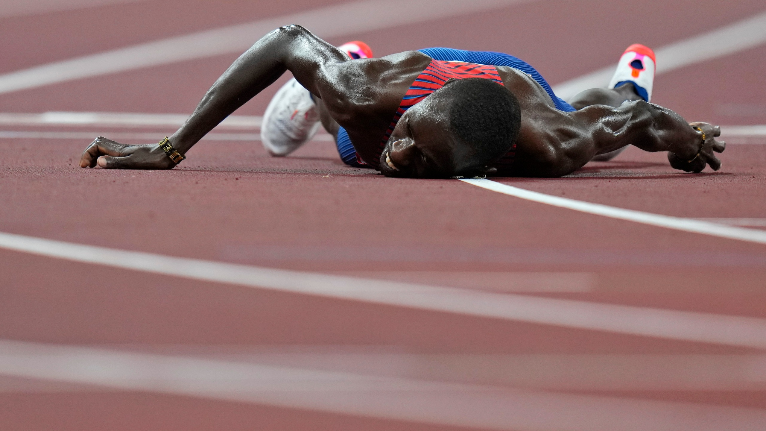 Paul Chelimo, of United States, lies on the track after the final of the men's 5,000-meters at the 2020 Summer Olympics in Tokyo.